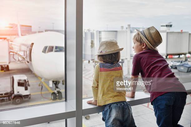 two children wearing straw hats looking through window to airplane on the apron - toddler at airport stock pictures, royalty-free photos & images