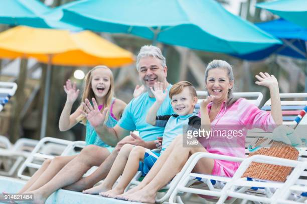 two children with grandparents on pool deck - poolside stock pictures, royalty-free photos & images