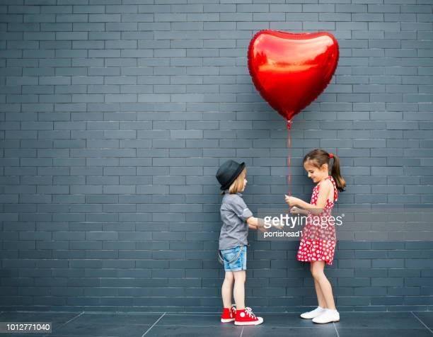 two children with heart shape air balloon - valentine's day holiday stock pictures, royalty-free photos & images