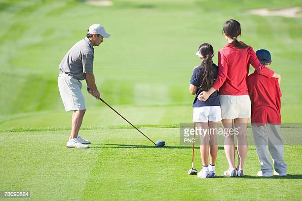Two children (8-10) with mother watching father playing golf
