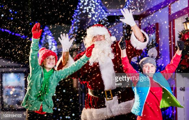 two children with santa claus at winter festival - florida christmas stock pictures, royalty-free photos & images
