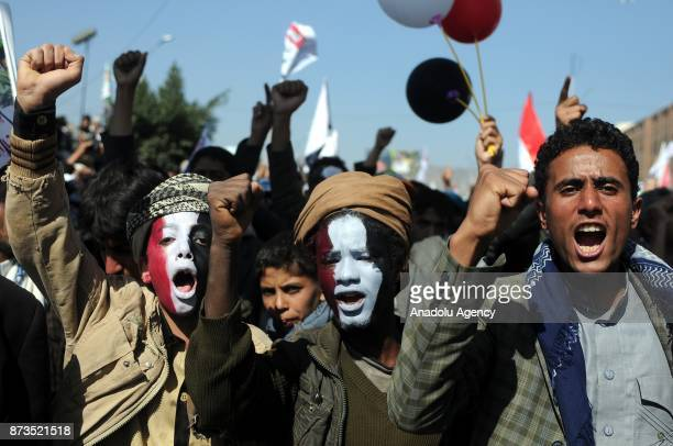 Two children with their faces painted in red white and black gesture during a protest over the closure of Yemen's borders in Sana'a Yemen on November...