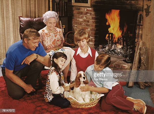 Two children with their parents grandmother and a pet spaniel circa 1975