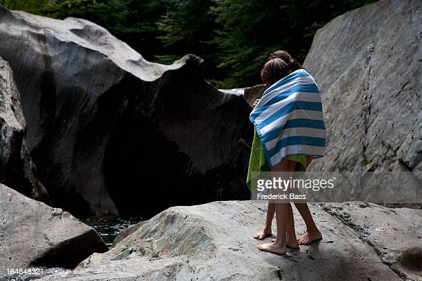 two children wrapped in towels and standing on rocks - big foot stock photos and pictures