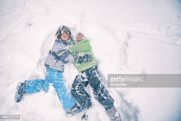 Two children wrestle playfully in the powdery snow
