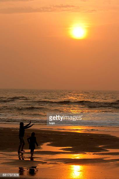 Two children's silhouette, play on the beach on the beach