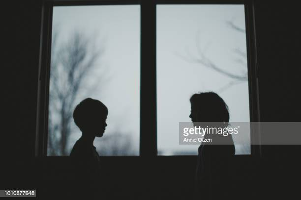 Two children's silhouettes in front of window