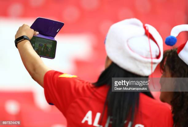 Two Chile fans take a selfie photograph on their phone prior to the FIFA Confederations Cup Russia 2017 Group B match between Cameroon and Chile at...
