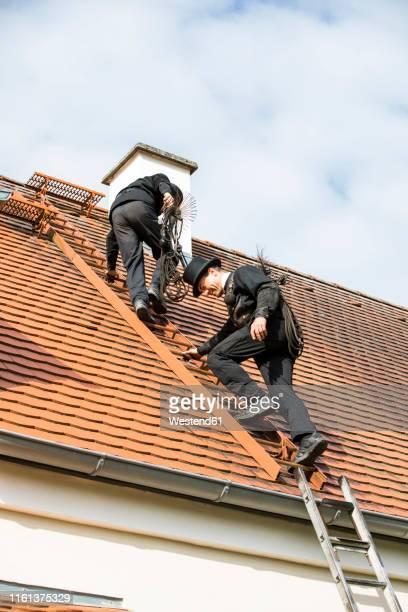 two chimney sweeps climbing up house roof - schornsteinfeger stock-fotos und bilder