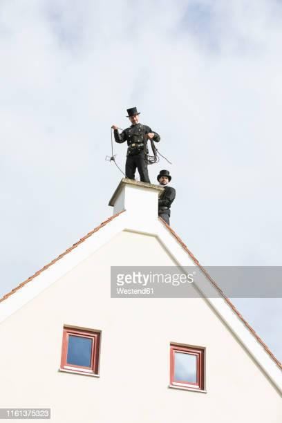 two chimney sweeps working on house roof - schornsteinfeger stock-fotos und bilder