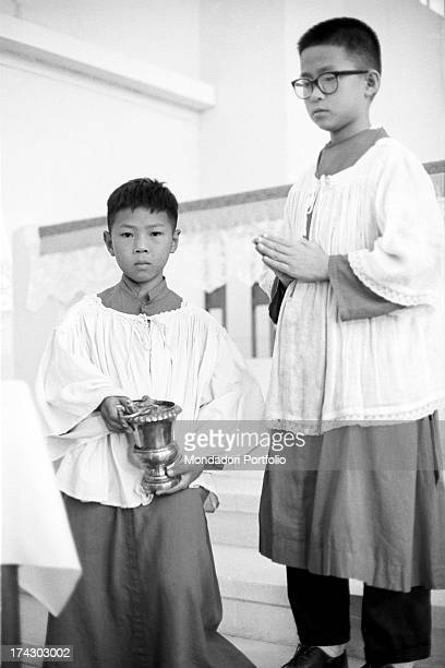 Two Chinese altar boys serving mass Hong Kong 1950s