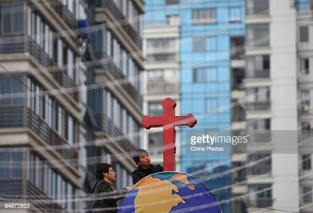Two Chinese catholics decorate a church with a cross on December 17 2009 in Wezhou of Zhejiang Province China Christmas continues to gain popularity...