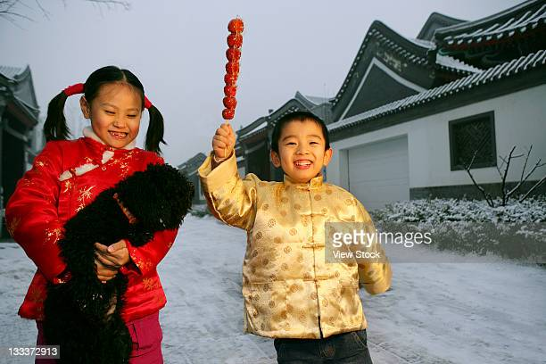 two chinese children playing with a black dog