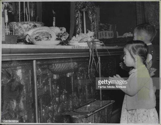 Two Chinese children praying for the blessings of the new year in a Joss House at Glebe The offering of food is seen an the altar before them January...
