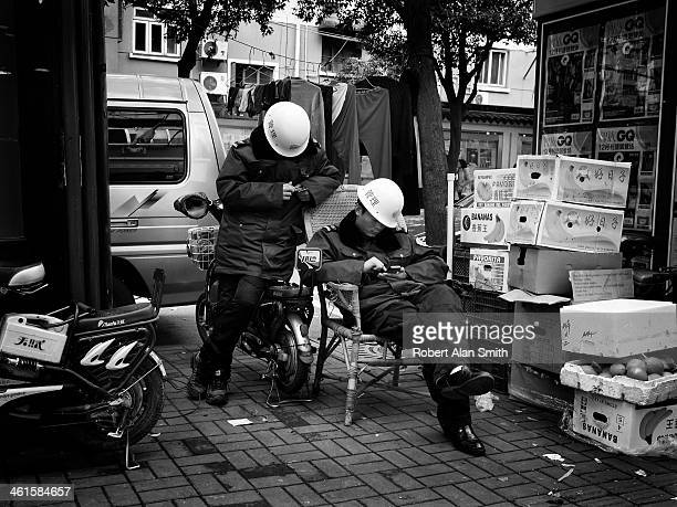 CONTENT] two Chinese city security guards taking it east and playing with their mobile phones captured on the streets of Shanghai