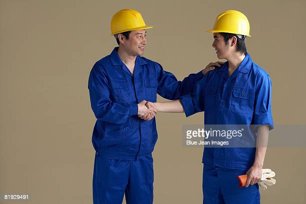 Two Chinese construction workers shaking hands