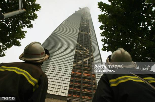 Two Chinese firemen look up at smoke coming from a fire at the 492 metres tall World Financial Center building which is under construction in the...