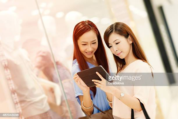 Two Chinese girlfriends in shopping mall