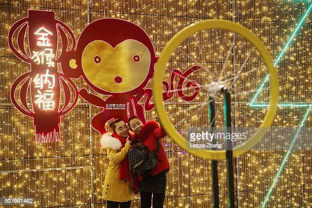 Two Chinese girls take a selfie in front decorations cartoon at a shop mall on January 27 2016 in Beijing China The Chinese Lunar New Year also known...