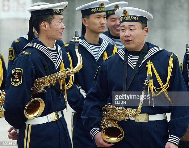 Two Chinese navy's bandsmen chat before the USS Blue Ridge arrives in Shanghai, 24 February 2004. The command ship of the US Navy's Seventh Fleet...