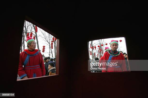 Two Chinese sedanchair bearers dressed in traditional clothes await customers aside their Chinese traditional sedanchair during a temple fair at the...