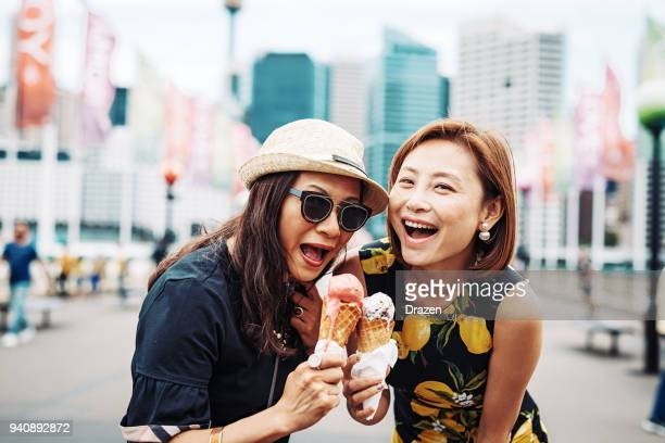 two chinese women enjoying ice cream - darling harbour stock pictures, royalty-free photos & images