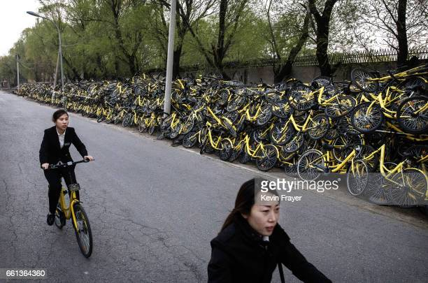 Two Chinese women ride bike share bicycles past piles of thousands of damaged bicycles from the bike share company Ofo Inc that were collected from...