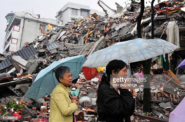 Two Chinese women weep in front of a collapsed building in Dujiangyan in southwest China Sichuan province on May 13 2008 after an earthquake...