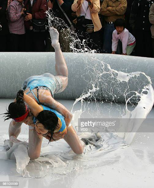 Two Chinese women wrestle in a mud pool during an international women's mud wrestling contest on March 28 2010 in Haikou Hainan province of China...