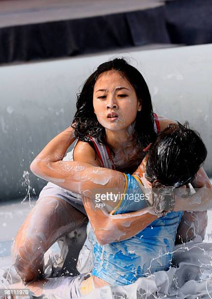 Two Chinese women wrestle in a mud pool during an international women's mud wrestling contest held in Haikou south China's Hainan island on March 28...