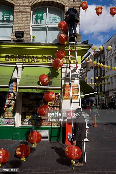 Two Chinese workmen work as a team attaching paper lanterns to an Oriental shop during preparations in London's Chinatown for the midAutumn Festival...
