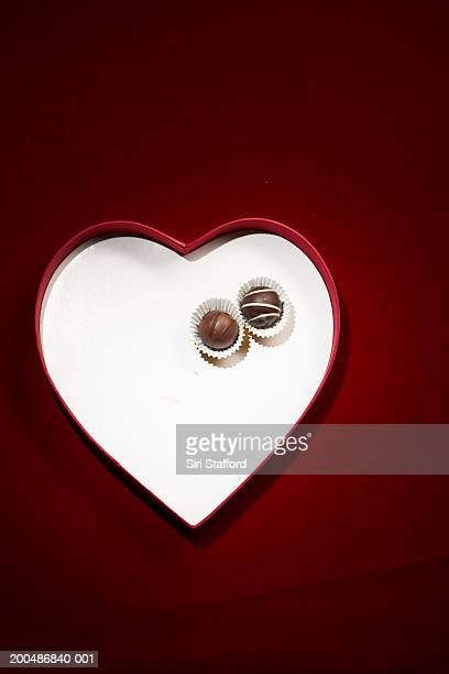 Two chocolate bon-bons in heart shaped box