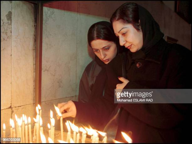 Two Christian girls light candels after general praying for Christmas time in St Sarkis church in Tehran