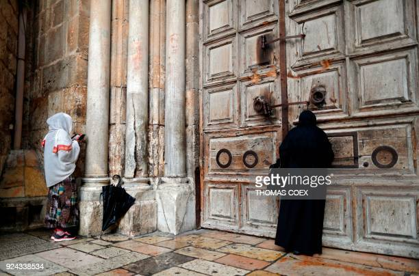 TOPSHOT Two Christian women pray by the closed door of the main entrance of the Church of the Holy Sepulchre in the Old City of Jerusalem on February...