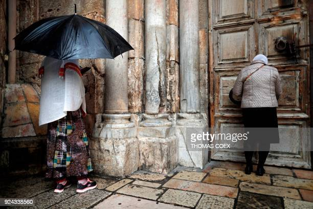 Two Christian women pray by the closed door of the main entrance of the Church of the Holy Sepulchre in the Old City of Jerusalem on February 26 2018...