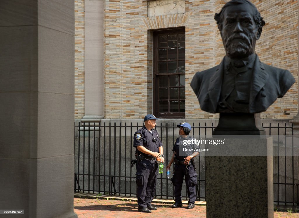 Two City University of New York Public Safety Department officers stand and monitor the area around a bust of Robert E. Lee as it stands in the 'Hall of Fame for Great Americans' on the campus of Bronx Community College, August 17, 2017 in the Bronx borough of New York City. On Wednesday night, the school announced the statues of Robert E. Lee and Confederate general Stonewall Jackson will be replaced and removed.