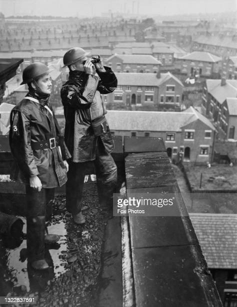 Two civil defence firewatchers of the Air Raid Precaution scan the sky with binoculars searching for German Luftwaffe bombers from the rooftop of a...