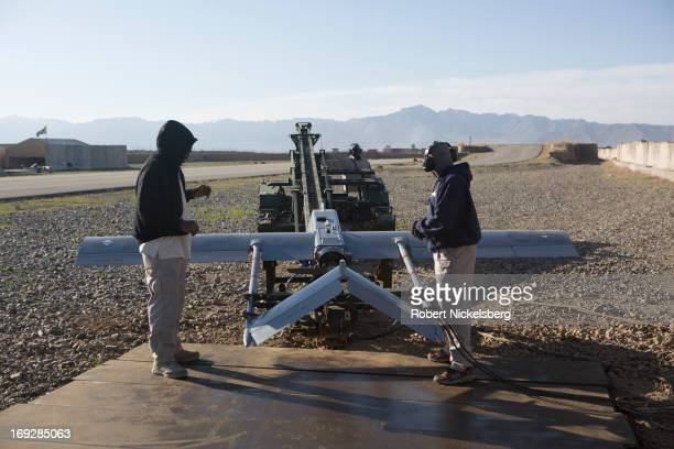 Two civilian contractors prepare a US Army 14' Shadow surveillance drone before it's launched at Forward Operating Base Shank May 8 2013 in Logar...