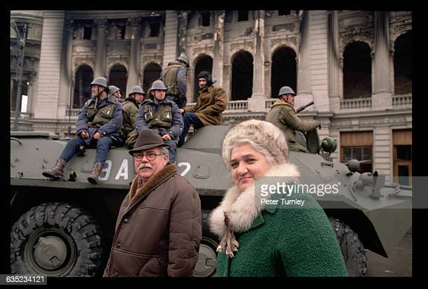 Two civilians walk past a manned tank in Palace Square in December 1989 in the thick of the weeklong revolution that resulted in the overthrow of...