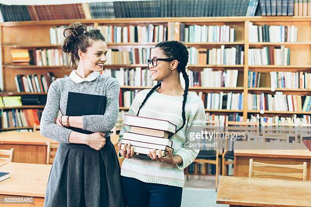 Two classmates meeting in the library