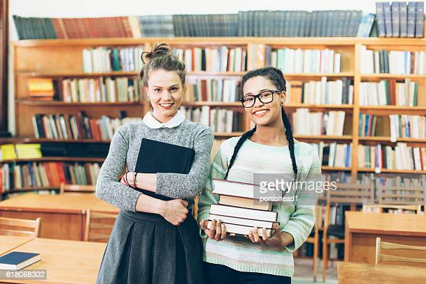 Two classmates standing in the library