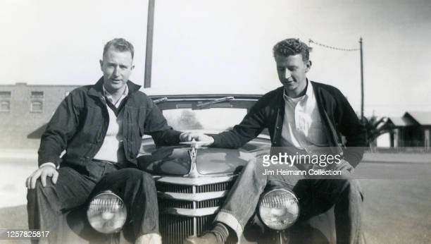 Two clean cut young men sit on the hood of a car holding hands, circa 1945.