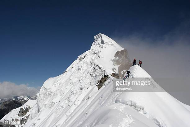 Two climbers almost at the top of a snowy mountain top