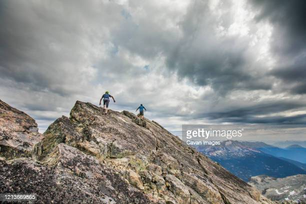 two climbers approach the summit of a mountain peak. - スクランブリング ストックフォトと画像