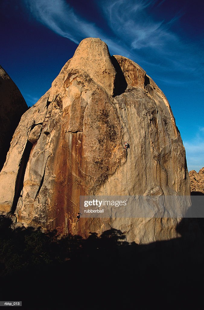 two climbers are scaling the side of a large rock formation with the sun shining on the face of it and a blue sky in the background : Stock Photo