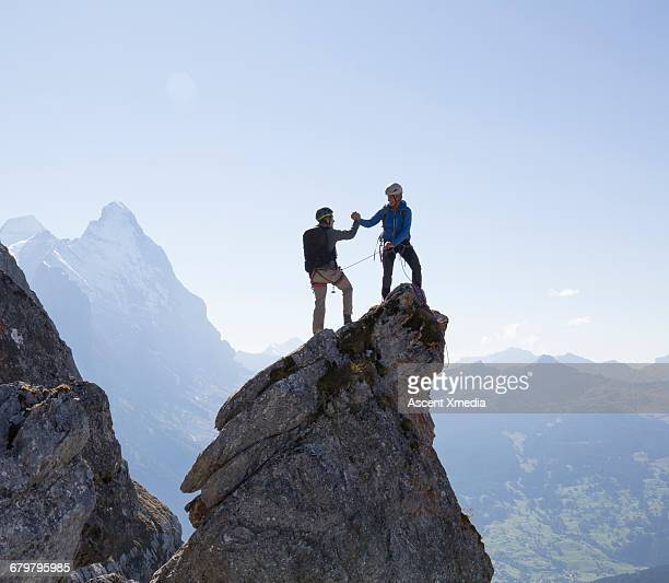 two climbers exchange handshake on pinnacle summit - leistung stock-fotos und bilder