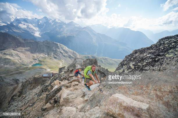 Two climbers making their way to the top gripping rocks and chains to mountain summit