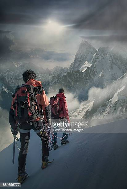 two climbers on a snowy slope watching the grand jorasses, in the mont blanc massif, chamonix, france - monte bianco foto e immagini stock
