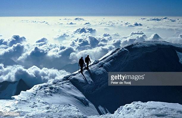 Two climbers on an icy ridge over the clouds