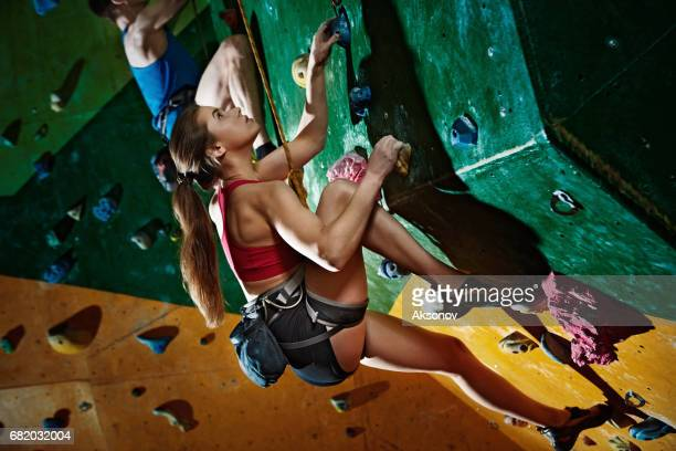 Two climbers purposeful climbs up the indoor climbing wall
